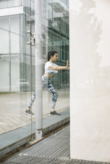 Young woman doing stretching exercise at glass facade - FMGF00092