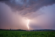 Lightning strikes over a field during a thunderstorm - INGF06177