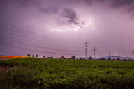 Lightning striking over an electricity pylon in a field - INGF06180