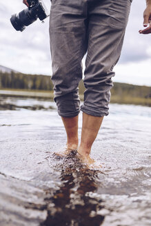 Sweden, Lapland, man with camera wading in water, partial view - RSGF00033