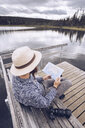 Sweden, Lapland, man with camera sitting on bench on a jetty looking at map - RSGF00039
