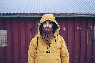 Sweden, Lapland, portrait of serious man with full beard wearing yellow windbreaker - RSGF00042