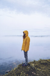Sweden, Lapland, man with full beard wearing yellow windbreaker standing at water's edge looking at distance - RSGF00045