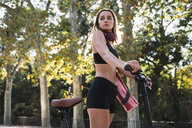 Fit young woman carrying yoga mat, riding bicycle - KKAF02908