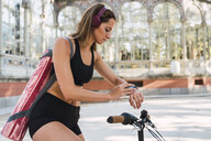 Fit young woman carrying yoga mat, riding bicycle - KKAF02911