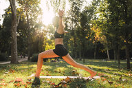 Fit young woman practicing yoga in a park - KKAF02932