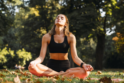 Fit young woman practicing yoga in a park - KKAF02941