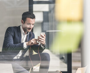 Businessman talking on the phone, using earphones - UUF15784