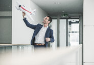 Laughing businessman playing with toy aeroplane in office building - UUF15799