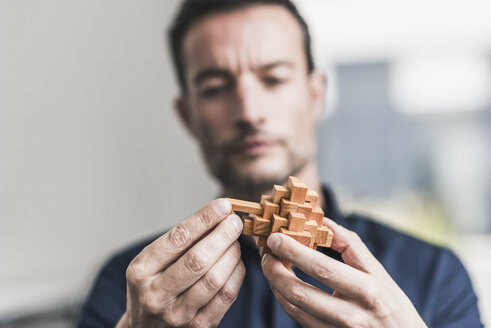 Mature man sitting in office assembling wooden cube puzzle - UUF15811