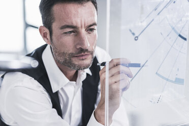 Businessman working in office, using futuristic computer with a transperant screen - UUF15850