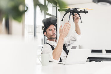 Businessman sitting in office working on a drone, using VR glasses - UUF15856