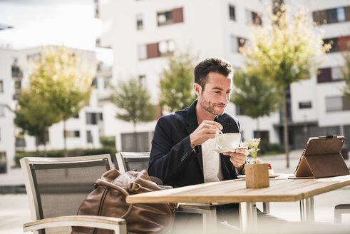 Businessman sitting in cafe, drinking coffee, using smartphone - UUF15874
