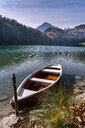 Germany, Bavaria, East Allgaeu, Fuessen, Alatsee, boat at lakeside in autumn - STSF01788