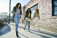 Three young women with long curly hair walking along pavement, one carrying skateboard. - MINF09101