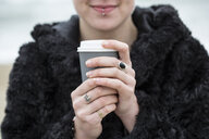 Close up of young woman wearing black furry jacket holding paper cup with hot drink. - MINF09161