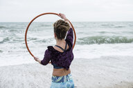 Young woman with brown hair and dreadlocks standing on a sandy beach by the ocean, balancing hula hoop. - MINF09164
