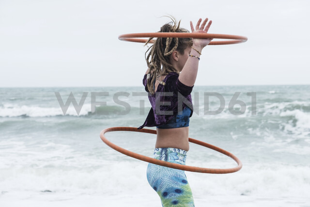 Young woman with brown hair and dreadlocks standing by the ocean, balancing two hula hoops. - MINF09167
