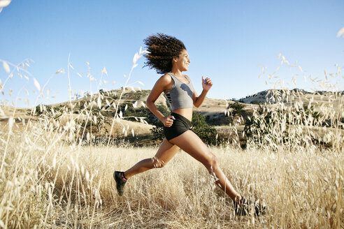 Young woman with curly brown hair running in urban park. - MINF09182