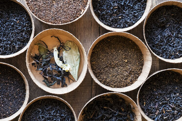 High angle close up of a selection of tea leaves in small wooden bowls. - MINF09362