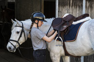 Teenage girl horse rider with a grey horse outside a stable, adjusting the girth and saddle. - MINF09386