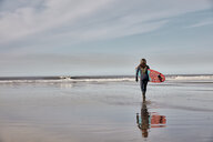 Man holding a surf board walking out to the sea at low tide. - MINF09392