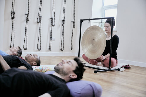 Woman using a gong during a sound therapy session and three people lying on their backs relaxing. - MINF09398