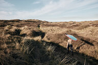 Man walking on a path in the sand dunes towards sea with surf board balancing on his head - MINF09401