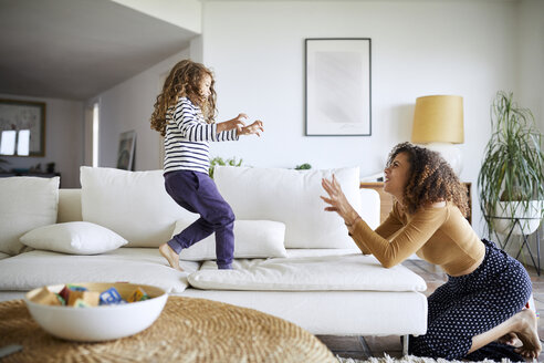 Side view of happy mother playing with daughter in living room - CAVF53221