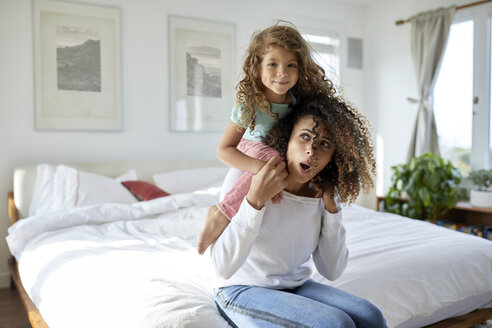 Portrait of daughter playing with mother sitting on bed at home - CAVF53239