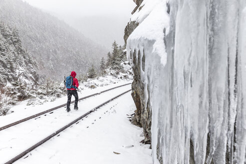Rear view of woman walking on snow covered railroad track during snowfall at White Mountains - CAVF53260