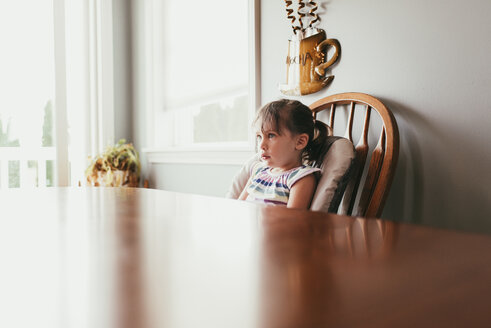 Thoughtful girl looking away while sitting on chair by wall at home - CAVF53272