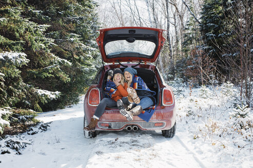 Cheerful female friends sitting in car trunk at Algonquin Provincial Park during winter - CAVF53281