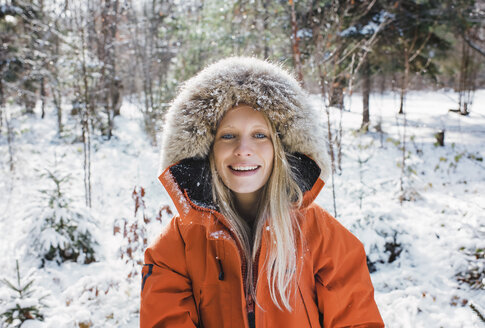 Portrait of smiling woman wearing fur coat in forest at Algonquin Provincial Park during winter - CAVF53284