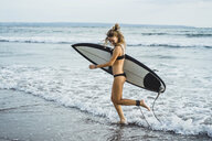 Side view of woman carrying surfboard while walking on shore at beach - CAVF53308