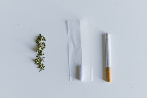 Overhead view of marijuana joints and cigarette with paper on white table - CAVF53320