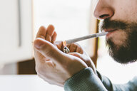 Midsection of bearded man igniting marijuana joint with cigarette lighter at home - CAVF53329