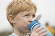 Close-up of boy looking away while drinking water against sky - CAVF53338