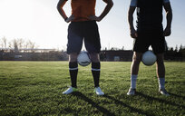 Low section of male friends with soccer balls standing on grassy field against clear sky during sunset - CAVF53356
