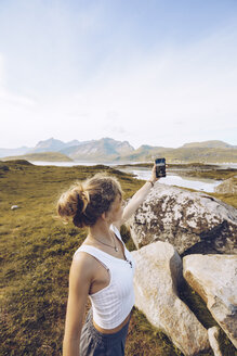 Norway, Lofoten, young woman taking selfie with smartphone in nature - RSGF00055
