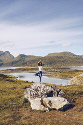 Norway, Lofoten, young woman standing on a rock on one leg doing yoga - RSGF00058
