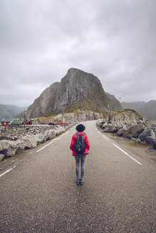 Norway, Lofoten, Hamnoy, back view of man with backpack standing on empty road - RSGF00067