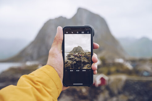 Norway, Lofoten, Hamnoy, hand holding smartphone for taking picture - RSGF00070