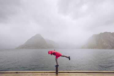 Norway, Lofoten, Hamnoy, man wearing red rain jacket balancing on wooden stake - RSGF00073