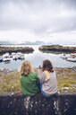 Norway, Senja, two young woman sitting at a small harbor with cell phone - RSGF00076