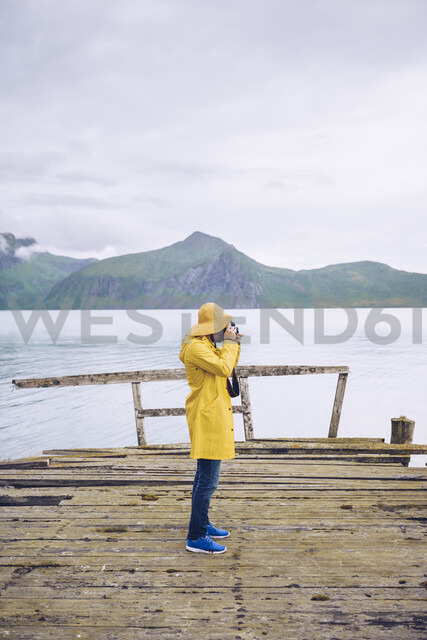 Norway, Senja, man standing on a ramshackle jetty at the coast taking a picture - RSGF00079 - CSSHOT/Westend61