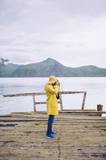 Norway, Senja, man standing on a ramshackle jetty at the coast taking a picture - RSGF00079