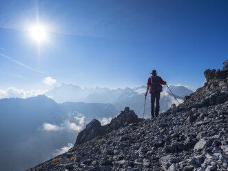 Border region Italy Switzerland, senior man hiking in mountain landscape at Piz Umbrail - LAF02145
