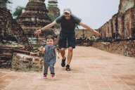 Thailand, Ayutthaya, Father and daughter running in the ancient ruins of a temple at Wat Mahathat - GEMF02472