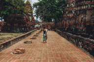 Thailand, Ayutthaya, Mother and daughter walking through the ancient ruins of a temple at Wat Mahathat - GEMF02478